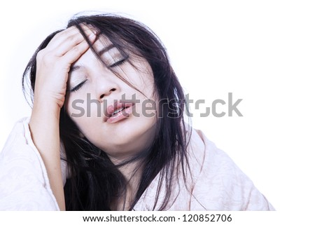 Woman is having bad headache by rubbing her forehead, isolated in white - stock photo