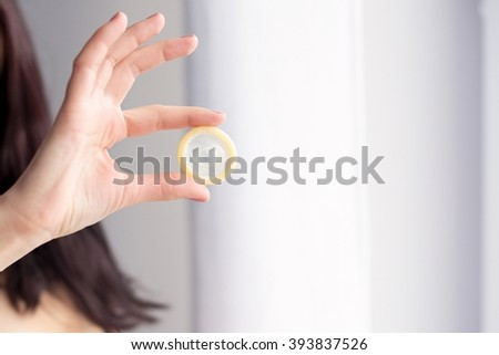 Woman is holding a condom for a safe sex. Safe sex concept  - stock photo