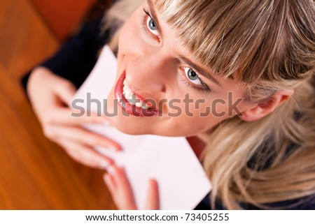 Woman is holding a love letter in her hands and looks happy - stock photo