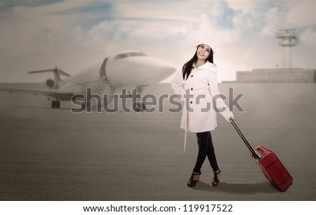 Woman is holding a suitcase to do a journey to the airport - stock photo