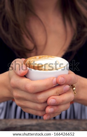 woman is holding cup of coffee - stock photo
