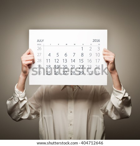 Woman is holding July calendar of the year two thousand sixteen.