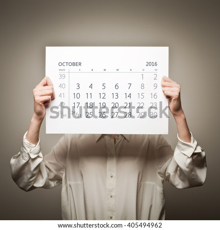 Woman is holding October calendar of the year two thousand sixteen.