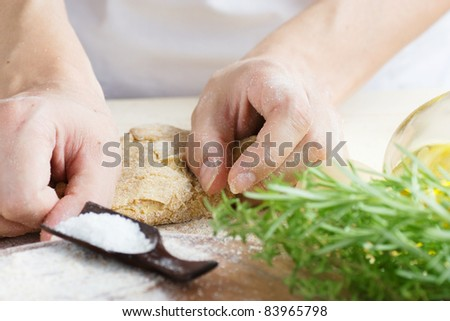 Woman is kneading dough balls for pizza or pastry, pasta preparation in the bakery . Ingredients for dough: Olive oil, salt and herbs with flour - stock photo