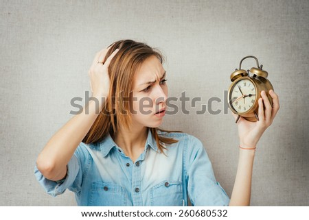 woman is late, watch in hand. isolated on gray background - stock photo