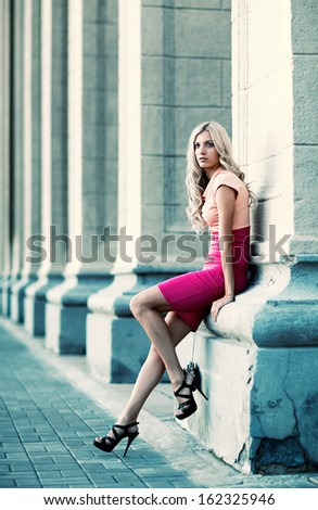 woman is leaning on a column outside of Novosibirsk academic opera theatre - stock photo