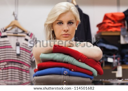 Woman is leaning on clothes in a boutique - stock photo