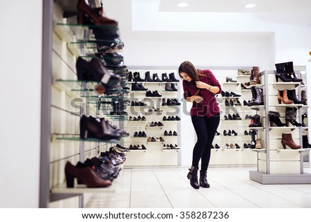 Woman is looking for a new pair of shoes. Shallow depth of field. - stock photo