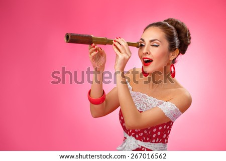Woman is looking through a telescope and making a surprised expression. She is standing against a pink background. - stock photo