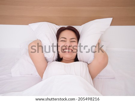 woman is lying in bed and covering her ears with pillow. Noise or insomnia concept.