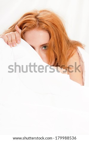 Woman is lying in bed under blanket and looking at camera - stock photo