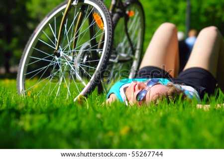 woman is lying near her bicycle - stock photo