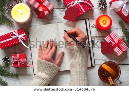 Woman is packing Christmas gifts. Red christmas gift boxes.