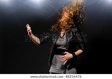 woman is playing rock music on air guitar - stock photo