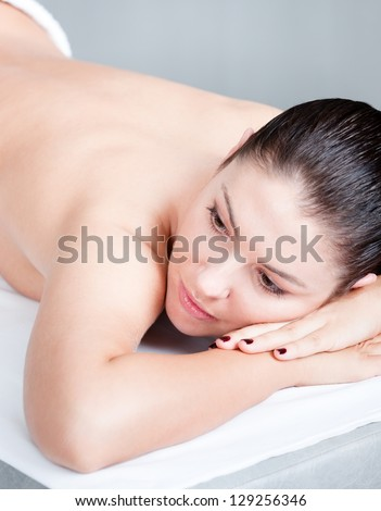 Woman is ready to receive relaxing body massage at spa salon. Healthy procedure - stock photo