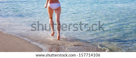 Woman is running ahead on beach of sea. Legs close-up