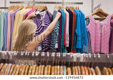 Woman is searching clothes in a boutique - stock photo