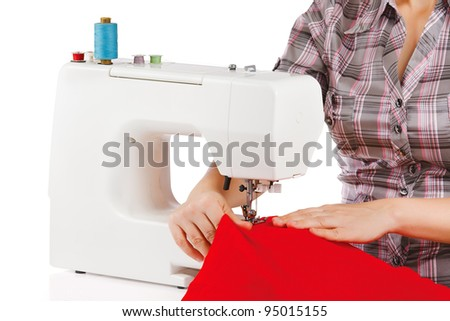 Woman is sewing on the sewing machine on a white background - stock photo