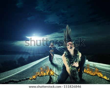 Woman is shooting into vampire's head action scene - stock photo