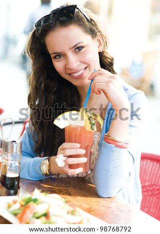Woman is sitting in cafe with cocktail and smiling at camera - stock photo