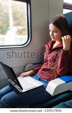 Woman is sitting in the train with laptop