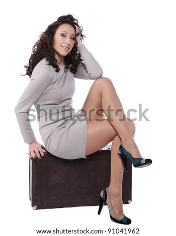 woman is sitting on old leather case