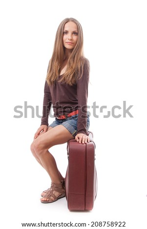 woman is sitting on old leather case, isolated on white