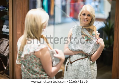 Woman is smiling in front of the mirror in the boutique - stock photo