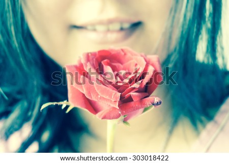 woman is smiling when she got a red rose , photo in cross process effect - stock photo