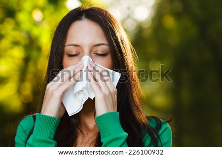 Woman is sneezing into handkerchief,Woman blowing nose - stock photo