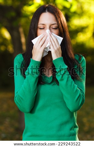 Woman is sneezing into handkerchief,Woman blowing nose