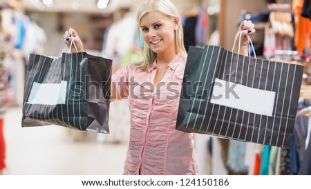 Woman is standing in a shop holding two bags - stock photo