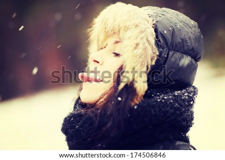 Woman is standing in the forest durring wintertime. Happy girl try to taste snowflakes.