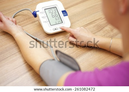 Woman is taking care for health with hearth beat monitor and blood pressure - stock photo