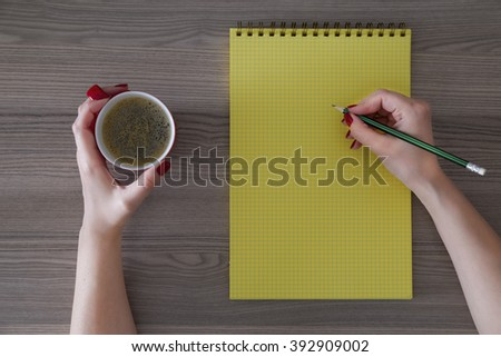woman is taking note on yellow notebook and drinking coffee