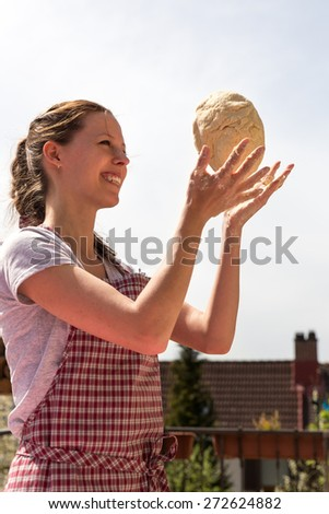 woman is throwing a dough ball, wearing a red white apron - stock photo