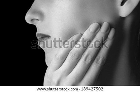 Woman is touching her cheek, toothache, black and white image - stock photo