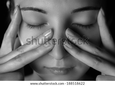 Woman is touching her nose and temporal region, woman is sick or tired