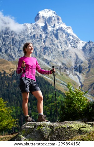 Woman is trekking Caucasus mountains in front of Ushba mount in Georgia - stock photo