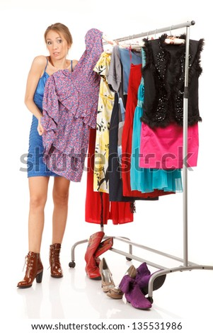 Woman is trying on dresses ;near her clothes rack with lots of dresses - stock photo