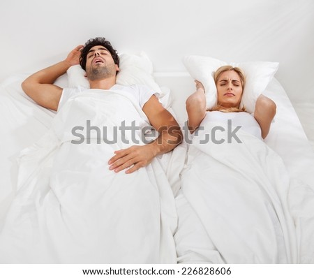 Woman is trying to fall a sleep while man is snoring. - stock photo