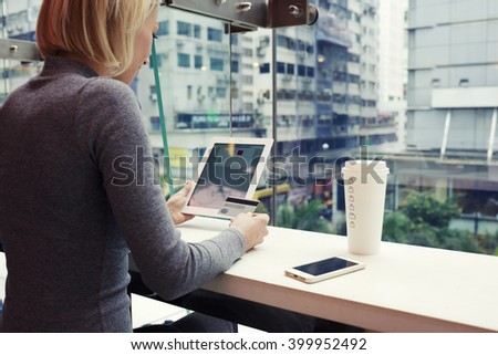 Woman is using credit card and touch pad for on-line booking ticket on plane to return from business trip from China. Female is making shopping in internet via digital tablet, while is sitting in cafe - stock photo