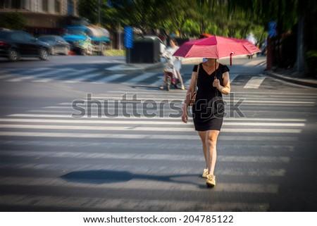 Woman is walking across the street at crosswalk - stock photo