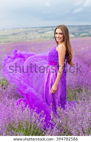 Woman is wearing fashion dress at lavender flowers - stock photo