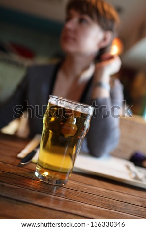 Woman is with glass of beer in a pub