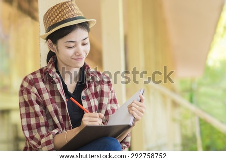 Woman is writing  in the book of her creativity. - stock photo