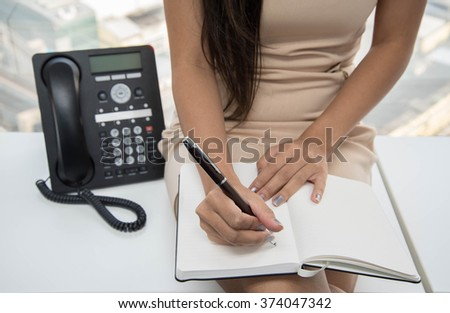 Woman is writing to notebook with IPPhone on the side