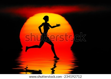 Woman jogging against a sunset ocean - stock photo