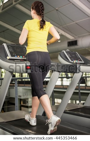 Woman jogging on treadmill at gym - stock photo