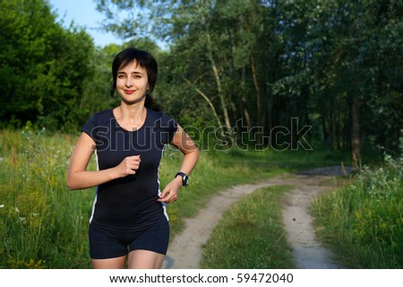 Woman jogging outdoors in summer forest - stock photo
